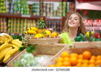 Beautiful girl chooses fruit at the grocery store