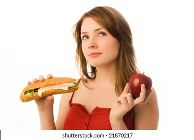 beautiful girl choosing between an apple and hot dog isolated against white background