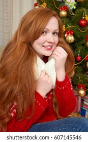 Beautiful girl in christmas decoration. Home interior with decorated fir tree and gifts. New year eve and winter holiday concept.