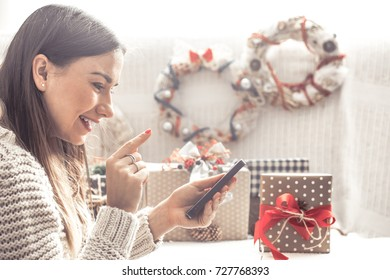 beautiful girl with Christmas gifts sitting on sofa and looks at the phone,the concept of Christmas shopping and congratulations