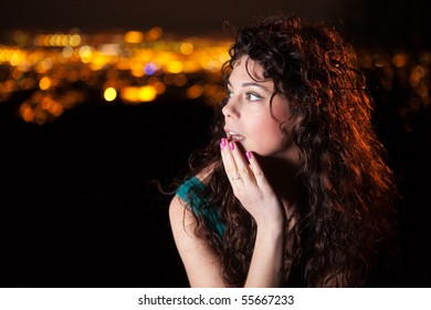 Beautiful girl with city lights in the background