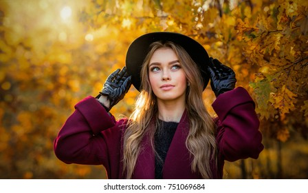 Beautiful  girl in claret coat and gloves standing near colorful autumn leaves. Art work of romantic woman .Pretty tenderness model in sun light on sunset looking down.