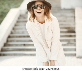 Beautiful girl close up with a hat laughing on a sunny day