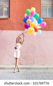 beautiful girl with closed eyes in pink dress  holds a bunch of balloons in front of old wall