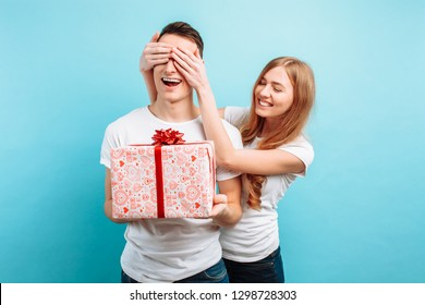 A beautiful girl closes the guy's eyes and gives him a gift, on a light blue background. Valentine's Day