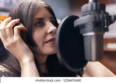 beautiful girl close-up recording a song in a professional Studio
