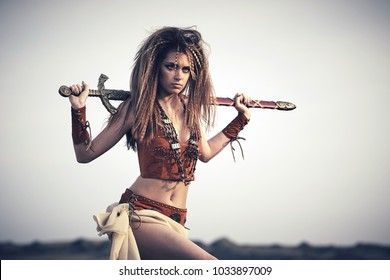 Beautiful girl in the clothes of a Viking or Amazon, with a sword on a background of sky. Closeup portrait.