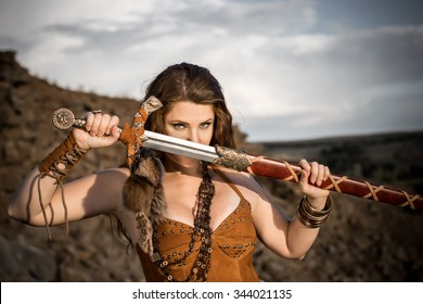 Beautiful girl in the clothes of a Viking or Amazon, with a sword on a background of stones.