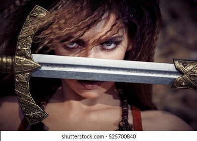 Beautiful girl in the clothes of a Viking or Amazon, with a sword on a background of stones. Closeup portrait.