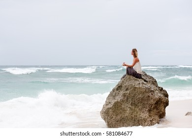 Beautiful girl clothing in white sit at the seaside on the rock and meditating in yoga woman pose