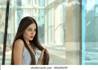 Beautiful girl clutched her hair in a fist. She has long brown hair and well-groomed skin. Portrait against glass and metal.