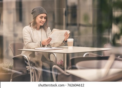 Beautiful girl in coat and cap is reading a newspaper and smiling while resting in a cafe outdoors