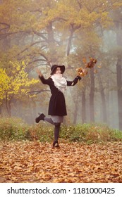 A beautiful girl in a coat and hat walks on the autumn forest