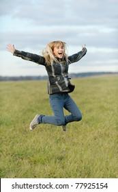 Beautiful girl in coat jumps against autumn field.