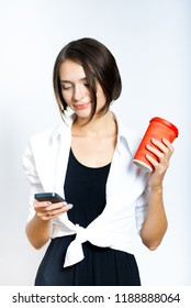 beautiful girl with a coffee and smartphone in hands, isolated over a white background