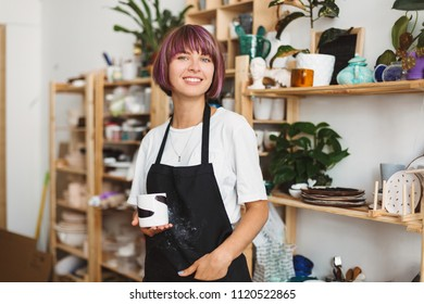 Beautiful girl with colorful hair in black apron and white T-shirt holding handmade mug in hand happily looking in camera spending time at pottery studio