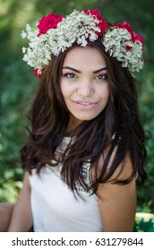 beautiful girl with colorful makeup and flowers in hair
