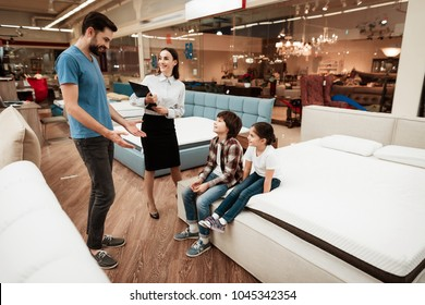 Beautiful girl consultant demonstrates orthopedic mattress to confident man with children in furniture store. Purchase of orthopedic mattress. Sale of orthopedic mattress in furniture store.