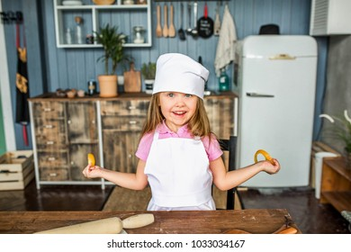 Beautiful girl in a cook costume smiles in the kitchen