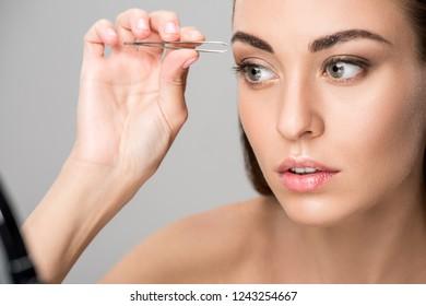 beautiful girl correcting shape of eyebrows isolated on grey
