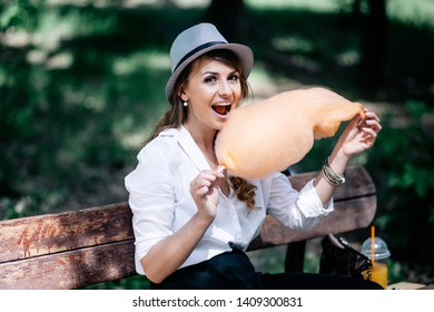 Beautiful girl with cotton candy in the park. Wearing a white shirt, dark pants and a hat. Good weather and cheerful mood.