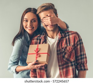 Beautiful girl is covering her boyfriend eyes and giving him a present, on gray background