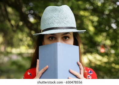 Beautiful girl covering her face with book; education and people concept;selective focus.