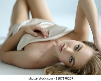 Beautiful  girl covers the naked sexy body. Gorgeous  woman lying and looking into camera. Nice portrait of a blonda girl with long curly hair.