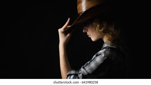 Beautiful girl in a cowboy's hat isolated on black background