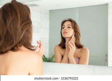 Beautiful girl with cream on face skin. Woman touching cheek with hand. Charming female  looking at mirror. Home bathroom. Facial health. Skincare and hygiene. Daily makeup