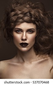 Beautiful girl with creative hairstyle art, perfect skin and dark makeup. The beauty of the face. Portrait shot in the studio.