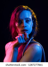 Beautiful girl with cretative make-up made of glitter with tears on her face wraps her neck with a metallic spiral hose illuminated with pink, blue and yellow light. Isolated on black. Copy space.