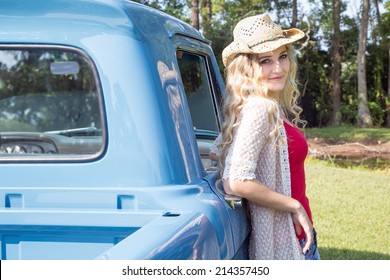 4f51dfa768d Beautiful girl with curly blonde hair leaning against a vintage truck  wearing a cowboy hat.