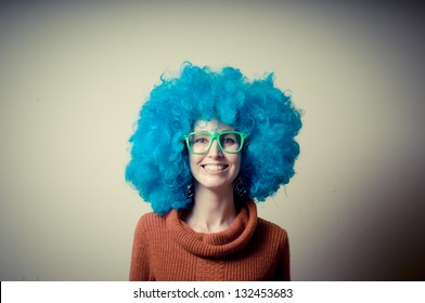 beautiful girl with curly blue wig and turtleneck on white background