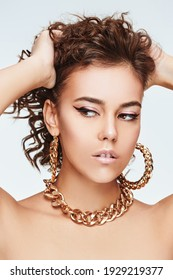 A beautiful girl with curly hair and elegant makeup poses with gold jewelry. Beauty and jewels. White background.