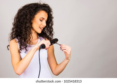 Beautiful girl  with curly hair iron straightener  happy and unhappy facial expression concept