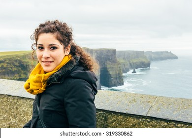 beautiful girl with curly hair on vacation to the cliffs of mohar