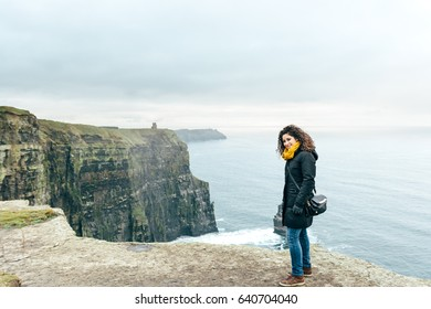 Beautiful girl with curly hair on vacation to the cliffs of Moher