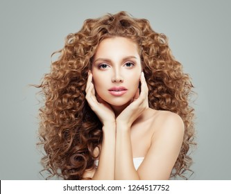 Beautiful girl with curly hair. Perfect female model face. Wavy hairstyle, haircare concept