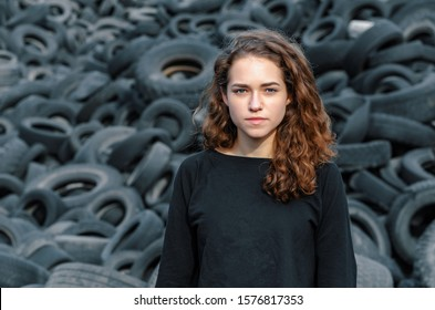 Beautiful girl, curly hair, portrait on the background of a dump of old car tires. Looking at camera.