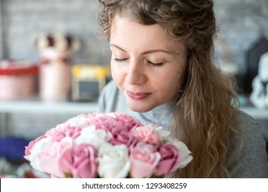 A beautiful girl with curly hair sniffs a fragrant bouquet of pink roses in a round box. Closed eyes.