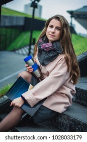 Beautiful girl, with curly long hair, wearing in white coat, blue scarf and gloves, holding cup of coffee and magazine and looking up, on the street of old European city, waist up