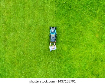 Beautiful girl cuts the lawn. Mowing lawns. Aerial view beautiful woman lawn mower on green grass. Mower grass equipment. Mowing gardener care work tool. Close up view. Aerial lawn mowing - Shutterstock ID 1437135791