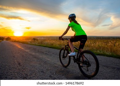 Beautiful girl cyclist riding a bike on the road towards the sunset. Nature and recreation. Hobbies and sports