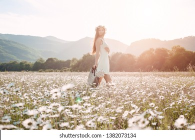 Beautiful girl in daisy field. Summer sunset. happy young lady and spring-green nature, harmony concept. Carefree happy brunette woman with healthy wavy hair having fun outdoor in nature.