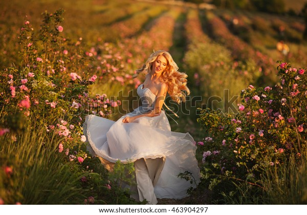 beautiful girl dancing in a field of roses
