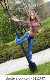 beautiful girl dancing on the street lamp pole in the park