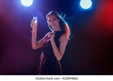 The beautiful girl dancing at the party drinking champagne