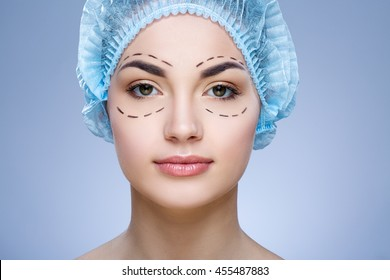 Beautiful girl with dark eyebrows and naked shoulders wearing blue medical hat at blue background and looking at camera, plastic surgery, portrait, perforation lines on face.