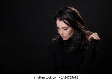 Beautiful girl with dark hair posing over black background. Young pretty woman in studio.
